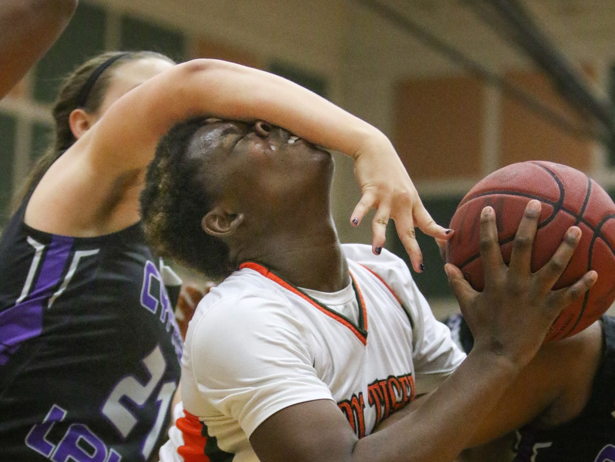 Dunbar's Ja'miah Bland (14) is fouled by Cypress Lake's Mackenzie Ackerman (21) during the ladies basketball game at Dunbar High School in Fort Myers, FL on Wednesday, January 27, 2016. Dunbar defeated Cypress Lake to win the District 12 Championship. Photo by Gregg Pachkowski