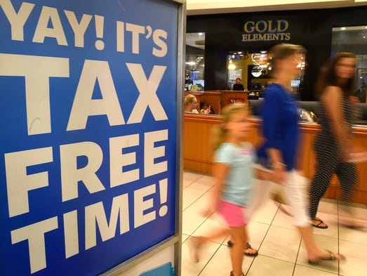 Customers pass by signs at Opry Mills advertising Tax-Free