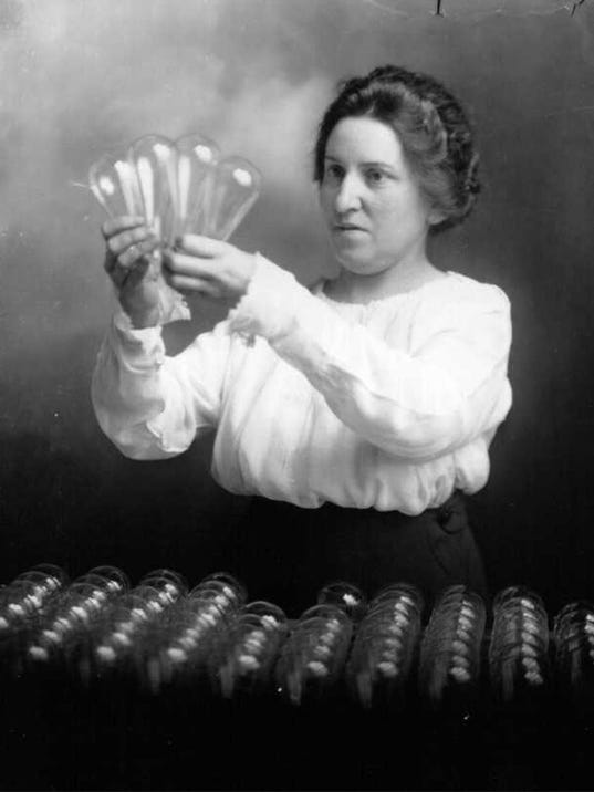 Woman inspecting lightbulbs