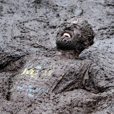 A competitor in the Mud Madness race, at Foymore Lodge in Portadown, County Armagh, Ireland. Some 800 competitors ran, crawled and belly-flopped their way across 4.5 miles of bogs and ponds, under cargo nets and through water sprays and muddy trenches for a cancer charity.