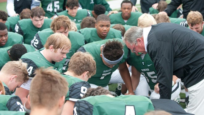 Trinity head football coach Bob Beatty prays with his team before the kickoff. September 2, 2017