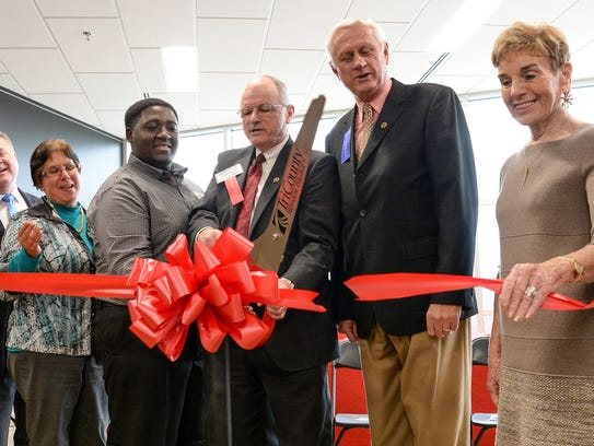President Ronnie Booth, middle, cuts ribbon near officials,