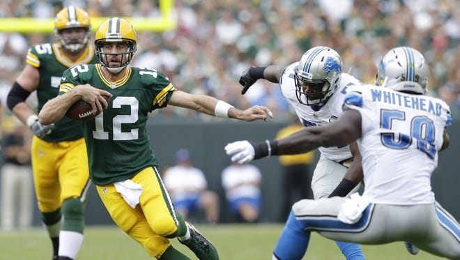 Green Bay Packers quarterback Aaron Rodgers runs for a first down past Detroit Lions defender Tahir Whitehead in the third quarter at Lambeau Field.