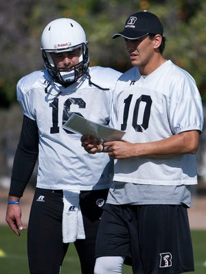 Quarterbacks BJ Coleman (R), 16, and Nick Davila (L), 11, of the Arizona Rattlers look over plays during practice at the Gene Autry Sports Complex in Mesa, Ariz., Wednesday March 11, 2015.