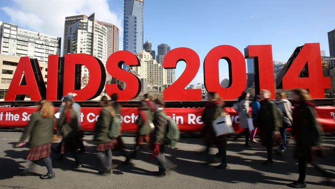Members of the public walk past signage on the Princes Bridge for the 20th International AIDS Conference on July in Melbourne, Australia.