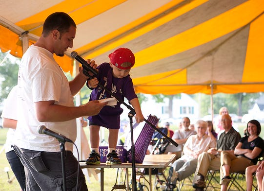 Travis Stargardt, left, speaks during the Relay for Life opening ceremony as his son Jay Stargardt, 3, right, adjusts the microphone at Beell Stadium in Marshfield, Friday, August 1, 2014. Jay Stargardt has survived neuroblastoma and leukemia and he and his father led the first lap of Relay for Life.