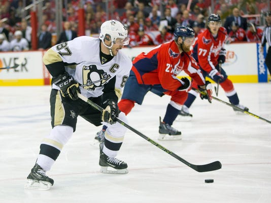 Pittsburgh Penguins center Sidney Crosby (87) skates past Washington Capitals defenseman Karl Alzner (27) and Washington Capitals right wing T.J. Oshie (77), during the first period of Game 1 in an NHL hockey Stanley Cup Eastern Conference semifinals Thursday, April 28, 2016 in Washington. (AP Photo/Pablo Martinez Monsivais)