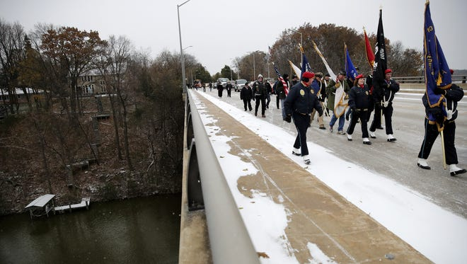 """Following the rededication and commemoration of """"The Spirit of the American Doughboy"""" statue on Memorial Drive on Saturday, attendees march with the American Legion Post 38's Scarlet Guard over the Fox River as they make their way to the Veterans Day ceremony at the Outagamie County Courthouse."""