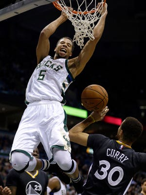 Milwaukee Bucks' Michael Carter-Williams (5) dunks over Golden State Warriors' Stephen Curry (30) during the second half of an NBA basketball game Saturday in Milwaukee. The Bucks won 108-95.