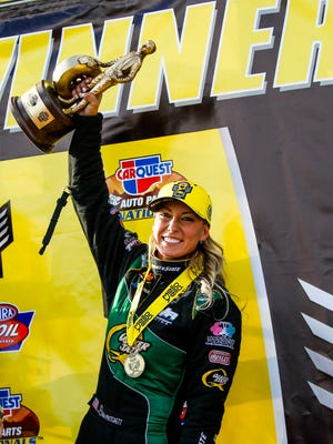 Top Fuel champion Leah Pritchett holds her trophy in the air after the finals of the Carquest Auto Parts NHRA Nationals on Sunday, Feb. 28, 2016, at Wild Horse Pass Motorsports Park near Chandler.