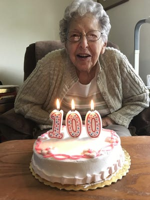 Former Two Rivers Public Schools fifth-grade teacher Miriam Olmsted blows out the candles on a cake celebrating her 100th birthday.