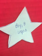 Items on each family's wish list is transferred to a paper star with the recipient's age and gender.
