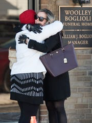 People embrace before entering the funeral home. Visitation