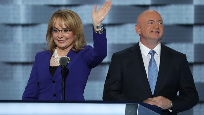 Former congresswoman Gabby Giffords waves to the crowd as her husband,  Mark Kelly, looks on after delivering remarks at the Democratic convention in Philadelphia on July 27, 2016.
