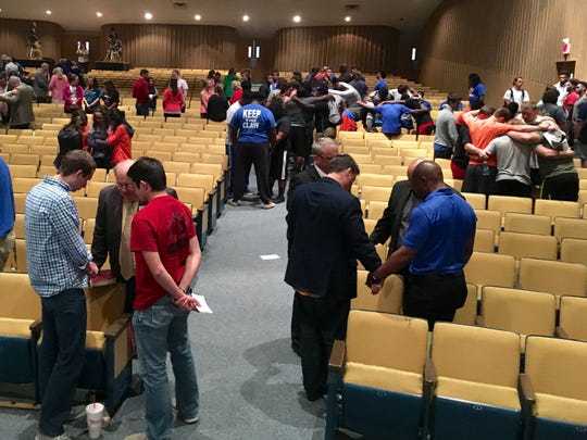 Louisiana College students, faculty, staff and trustees pray Monday in groups of three in Guinn Auditorium on the campus in Pineville.