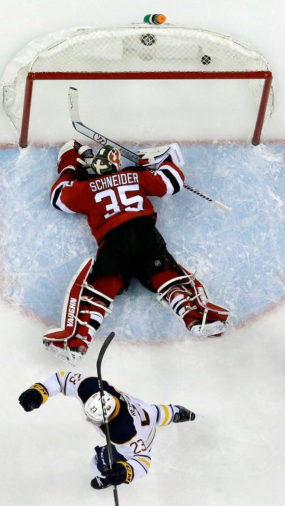 New Jersey Devils goalie Cory Schneider (35) lays on the ice after a shot by Buffalo Sabres center Jack Eichel, not pictured, entered his net for a goal as teammate Sam Reinhart (23) celebrates during the third period of an NHL hockey game, Friday, Dec. 29, 2017, in Newark, N.J. The Sabres won 4-3 in overtime. (AP Photo/Julio Cortez)