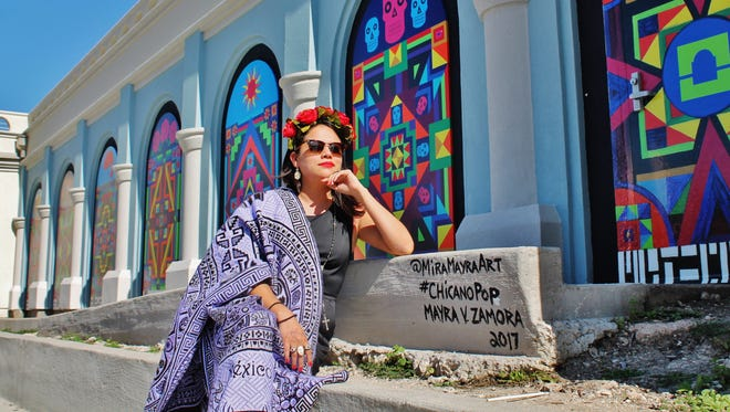 Mayra Zamora poses in front of her Chicano Pop mural at the Art Center of Corpus Christi.
