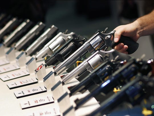 FILE - In this Jan. 19, 2016, file photo, handguns are displayed at the Smith & Wesson booth at the Shooting, Hunting and Outdoor Trade Show in Las Vegas. The gun industry is gathering for its annual conference, in January 2020, amid a host of uncertainty: slumping gun sales, a public increasingly agitating for restrictions on access to firearms and a presidential campaign that threatens gun rights like perhaps no other time in modern American history. (AP Photo/John Locher, File)