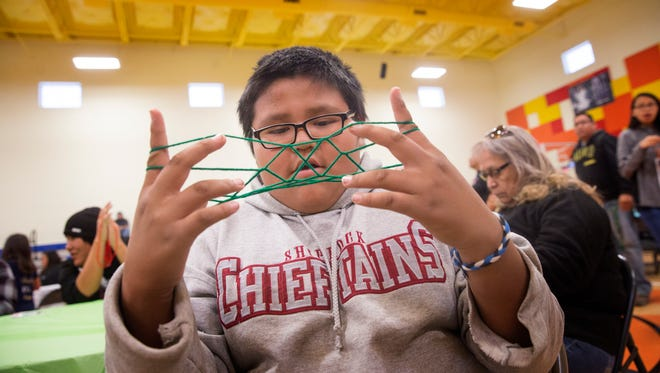 Terrell Shirley participates in a string game Wednesday during the Restoring and Celebrating Family Wellness program at the Office of Diné Youth in Shiprock.