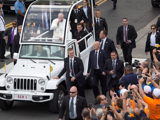 Pope Francis greets the crowd from the Pope Mobile