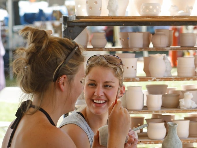 Danica Edginton (center) laughs with Taylor Estabrook while glazing raku in the Artisan Village during the Oregon State Fair on Tuesday, Aug. 26, 2014.