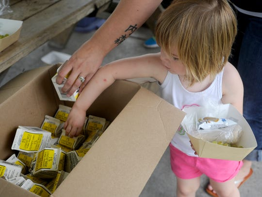 Nora Arnes, 2, gets milk from a box to go along with her lunch.