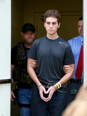 Austin Harrouff is transported by detectives to the Martin County Jail from St. Mary's Hospital on Monday, Oct. 3, 2016.   The college student who deputies say bit a dead man's face after stabbing him and his wife to death outside their Florida home was released from the hospital Monday and taken to jail almost two months after the attack. (Richard Graulich/Beach Post via AP)
