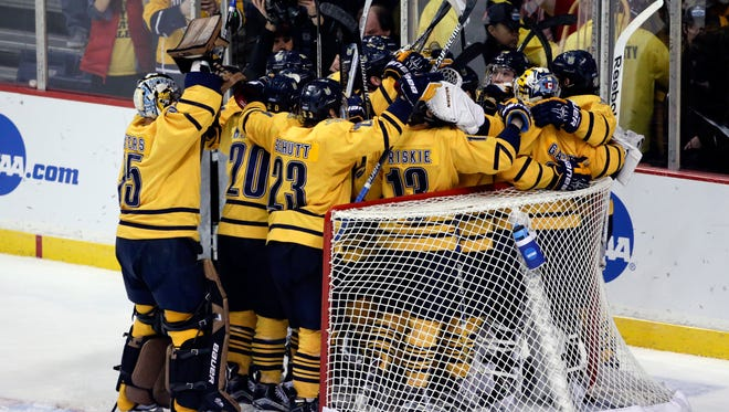 Quinnipiac players celebrate their 4-1 win over UMass Lowell in the NCAA men's East Regional championship hockey game on Sunday, March 27, 2016, in Albany, N.Y. (AP Photo/Mike Groll)