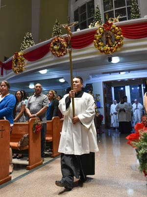 An altar server carries a processional cross during the Dulce Nombre de Maria Cathedral-Basilica Christmas midnight mass in Hagatna on Dec. 25, 2016.