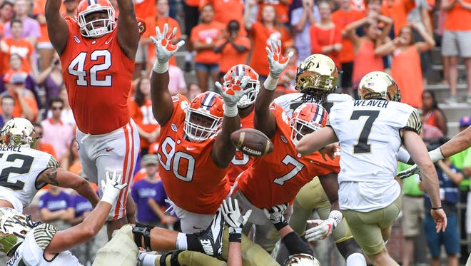 Clemson defensive tackle Christian Wilkins (42), defensive lineman Dexter Lawrence (90), and defensive end Austin Bryant (7) lunge as Wake Forest kicker Mike Weaver (7) misses a field goal during the third quarter in Memorial Stadium at Clemson on Saturday.