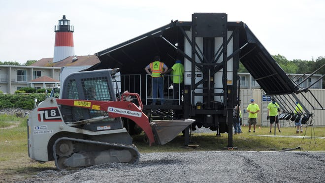 A foundation is leveled for movie screens Tuesday as the former drive-in theater site along Parkers River in West Yarmouth is converted into an entertainment center featuring three high-definition LED screens and a stage. The complex is slated to open Sunday.
