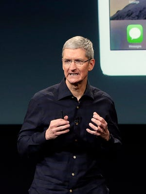 File-This Oct. 16, 2014, file photo shows Apple CEO Tim Cook introducing the new Apple iPad Air 2 during an event at Apple headquarters in Cupertino, Calif.