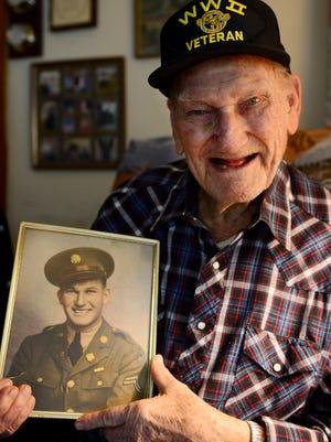 World War II Veteran Raymond Osborne holds his United States Amry photo at his home in Jackson.