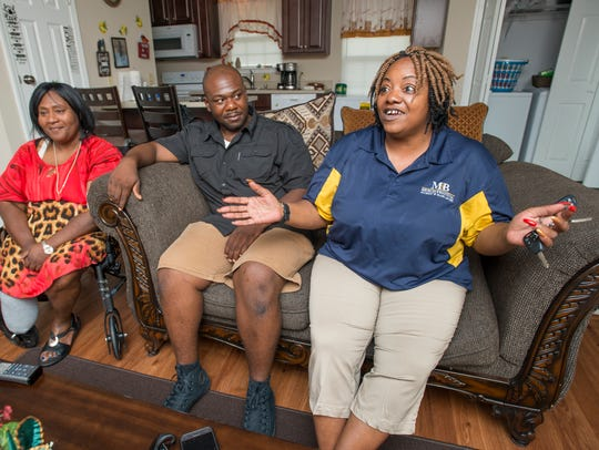 Jamie Scott, left, and her son, Richard Scott, listen as Gladys Scott talks July 16 about adjusting to life outside prison from their home in Pensacola.