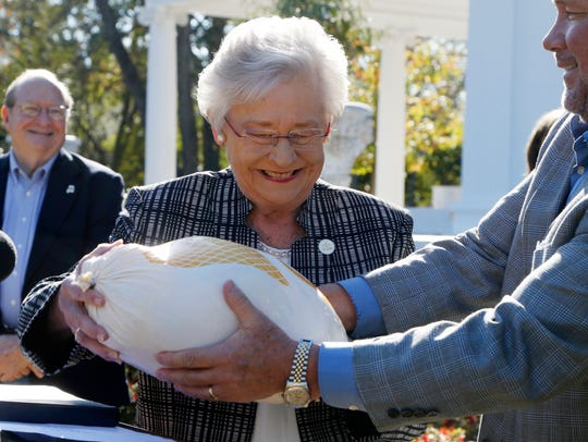 Gov. Kay Ivey receives a turkey during the 68th annual