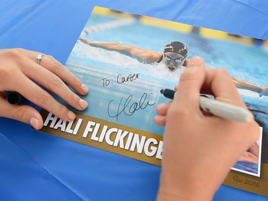 Rio Olympic swimmer Hali Flickinger signs an autograph