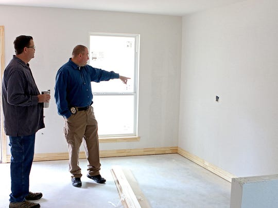 Brad Love (left) and Brian Bohn look over detail work that still needs to be done on a home they are helping build on Pennsylvania Road for Maxine.