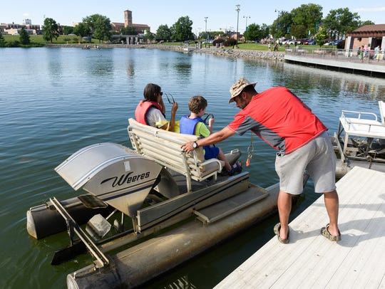 Jose Rivera gives a paddleboat a push off from the
