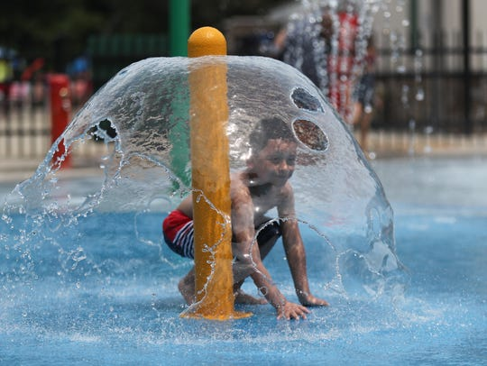 A young boy enjoys a fountain on the splash mat at