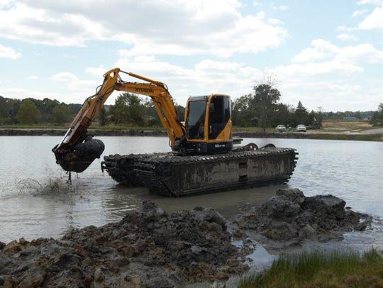 A Hyundai R60 amphibious track machine dredges silt