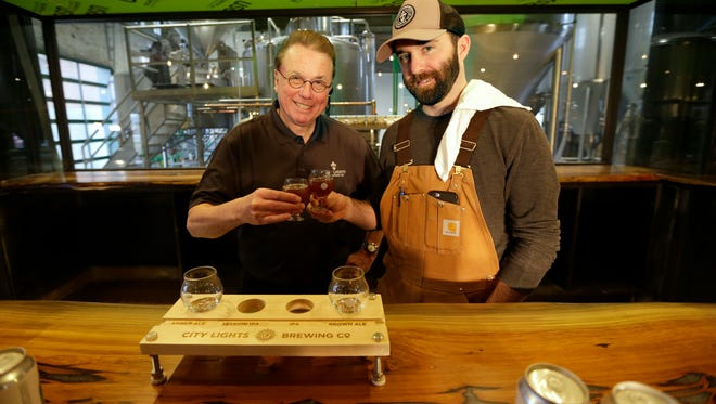 David Ryder (left), City Lights Brewing's chief innovation officer, and Jimmy Gohsman, City Lights Brewing's brewmaster, toast with a sample of beer in what will be the bar area at the new Menomonee Valley craft brewery at 2210 W. Mount Vernon Ave., in the former Milwaukee Gas Light building.