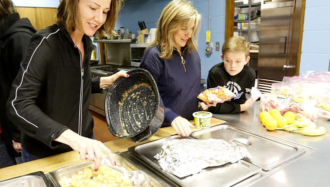 Salvation Army volunteers Jenni Slinde and Linda and Jamie Ahern get a hot meal ready for the opening day the facility's warming shelter, Tuesday November 1, 2017. Doug Raflik/USA TODAY NETWORK-Wisconsin