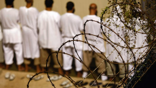 Detainees stand during an early morning Islamic prayer at the U.S. military prison for enemy combatants on Oct. 28, 2009, at Guantanamo Bay, Cuba.