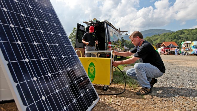 Joe Sadonis, a solar analyst for Sigora Soloar of Waynesboro, sets up a display at the Music for the Mountains festival at Devil's Backbone Brewery in Roseland on Saturday, July 18, 2015.