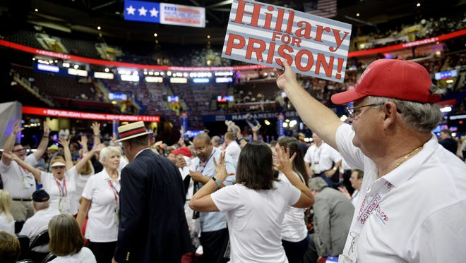 A delegates waves an anti-Hillary Clinton sign on the second day of the Republican National Convention on Tuesday, July 19, 2016, at Quicken Loans Arena in Cleveland. (Olivier Douliery/Abaca Press/TNS)