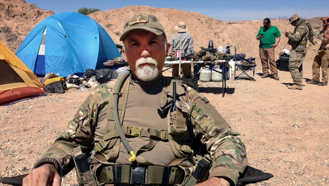 In this April 16, 2014 file photo, Jerry DeLemus, of Rochester, N.H., sits with a group of self-described militia members camping on rancher Cliven Bundy's ranch near Bunkerville, Nev.