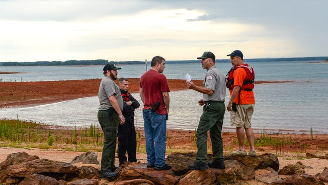 Scott Lusk, middle right, U.S. Army Corps of Engineers Park Ranger, talks with Ryan Herring, middle left, Coordinator of Anderson Technical Rescue Team, as emergency rescue workers and divers search for a man who fell over a boat in Lake Hartwell Saturday afternoon.