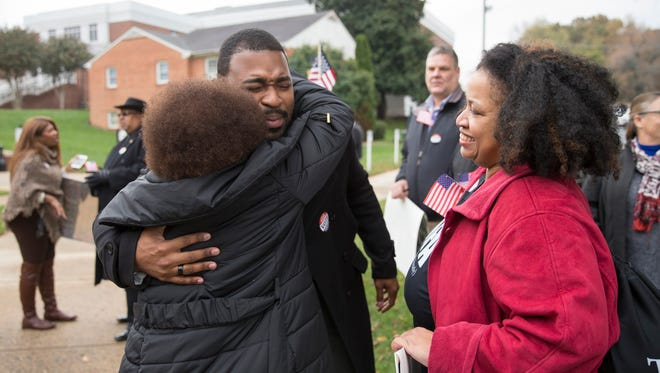 Joshua Cole, Democratic candidate for delegate in the 28th district, gets a hug from Rachel Campbell, secretary of the Stafford NAACP, outside the Stafford County Government building in Stafford, Va. on Monday, Nov. 13, 2017. Protesters gathered to call on the registrar to count all absentee ballots.