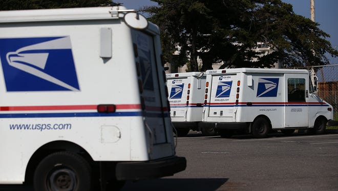 U.S. Postal Service mail vehicles sit in a parking lot at a mail distribution center on February 18, 2015 in San Francisco, California.