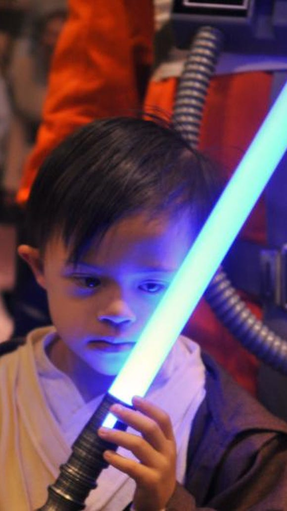 """""""Young Jedi"""" Preston Todaro, 6, of Fort Lauderdale admires a light saber from Ra Kura Base, the Florida group of the Rebel Legion """"Star Wars"""" costuming club, at MegaCon in Orlando."""